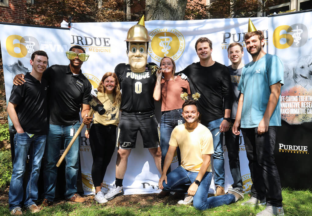 students gather around Purdue Pete against a photo backdrop donning party hats and accessories in the courtyard