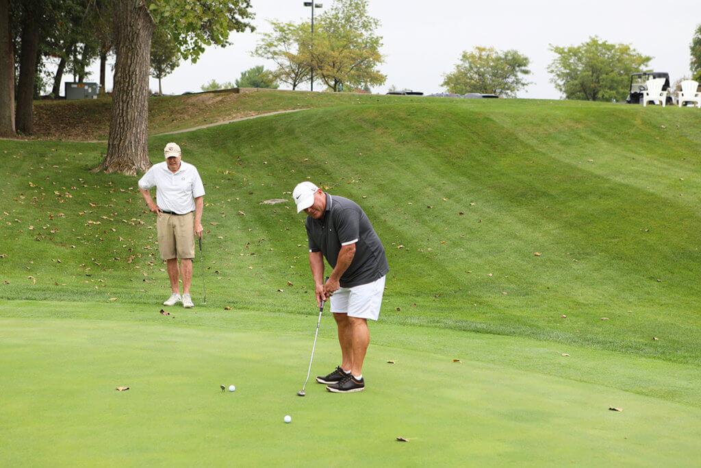 A golfer gears up to putt while a fellow participants looks on