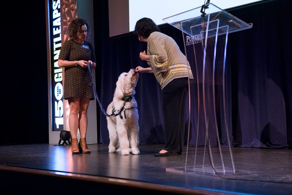 Jennifer gives Robb the service dog a treat on stage as his owner holds his leash