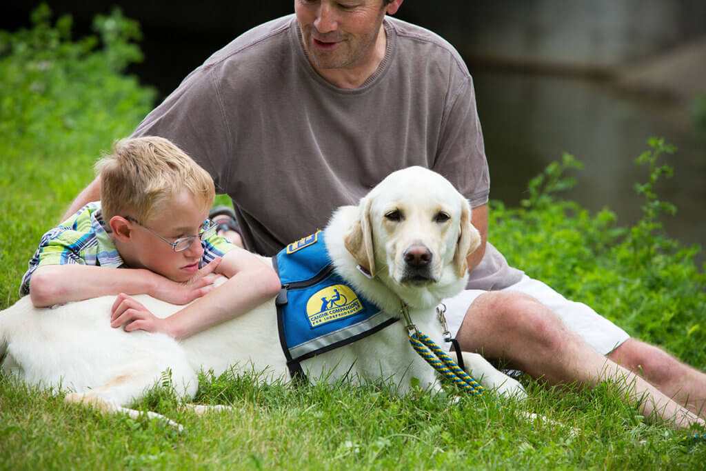 A boy leans on his service dog in the grass beside his dad