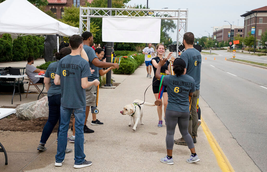 Student volunteers congratulated runners and their dogs as they crossed the finish line in front of Lynn Hall.