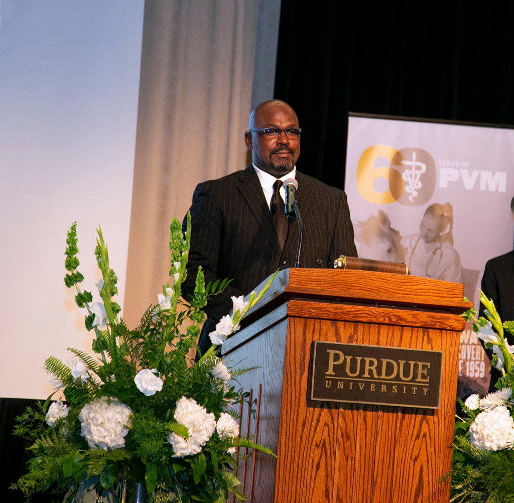 Dr. Ragland speaks from a podium on stage during the Awards Celebration Dinner in the Purdue Memorial Union ballroom