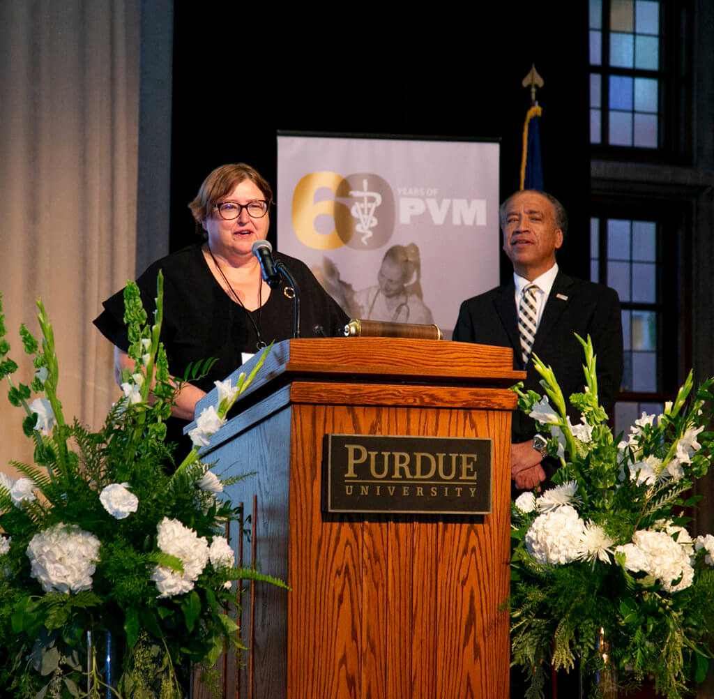 Dr. Krtichevsky speaks from the podium on stage as Dean Reed looks on