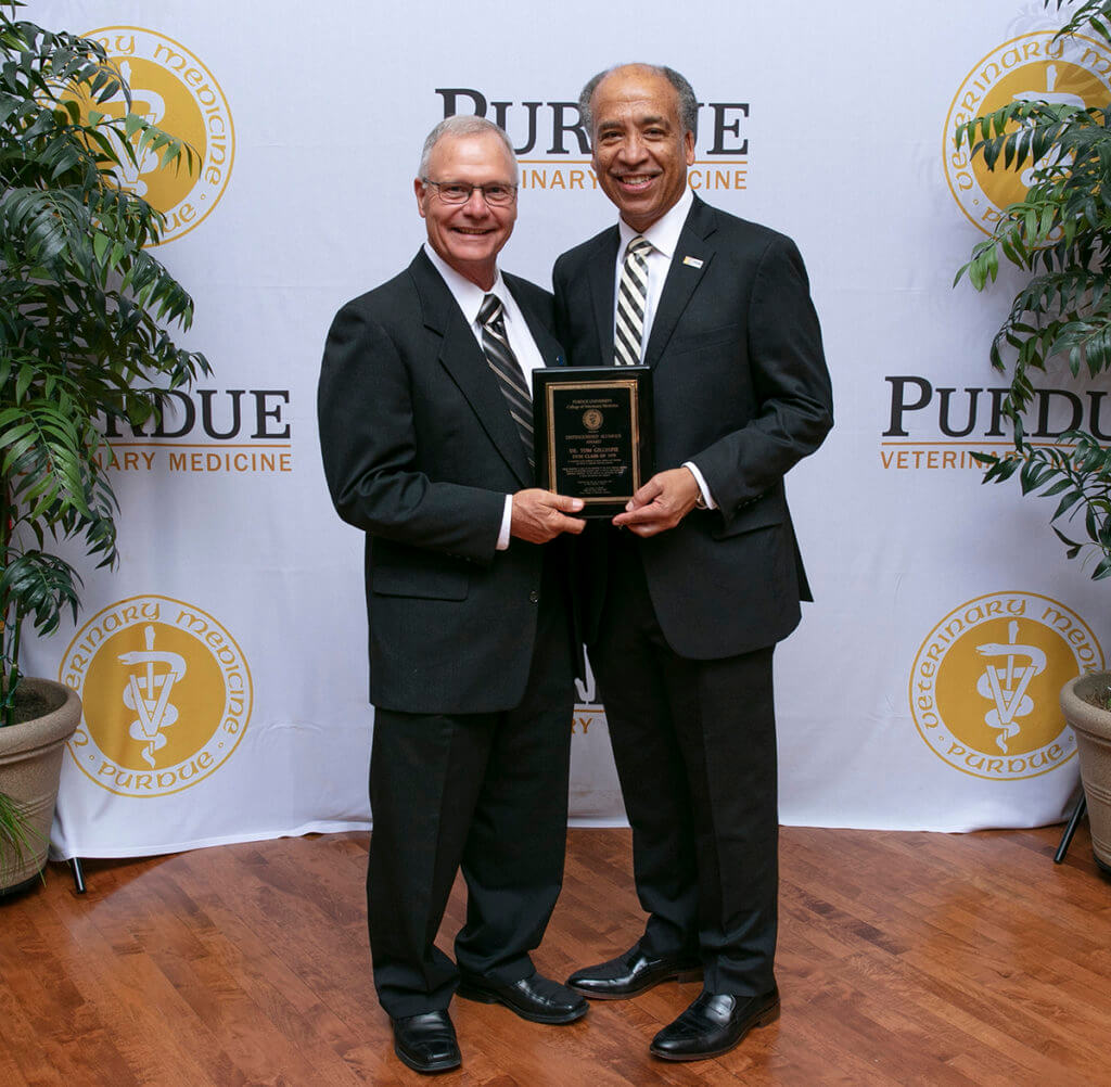 Dr. Gillespie stands with Dean Reed holding his award plaque