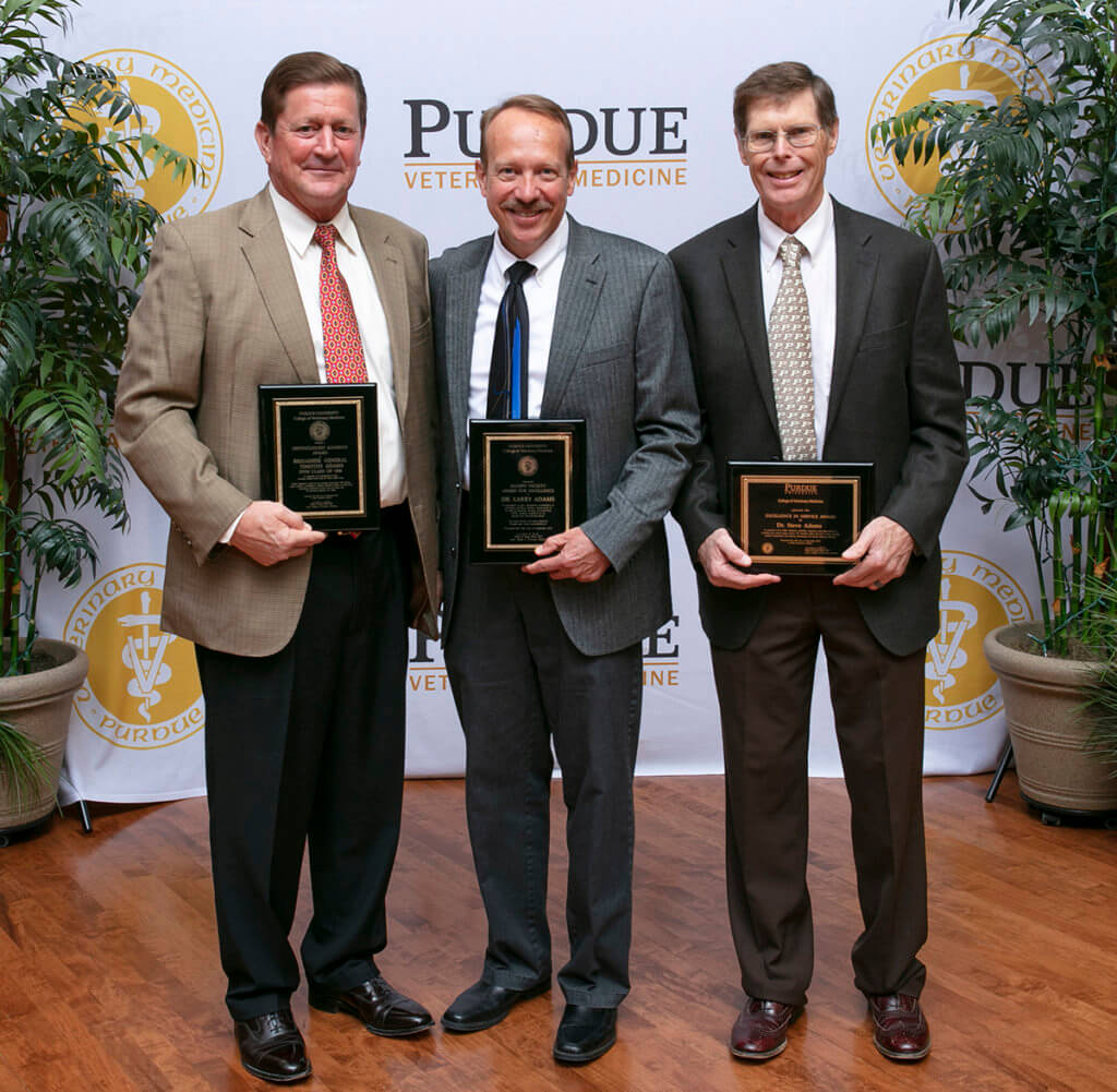 Drs. Timothy Adams, Larry Adams, and Steve Adams stand together holding their award plaques