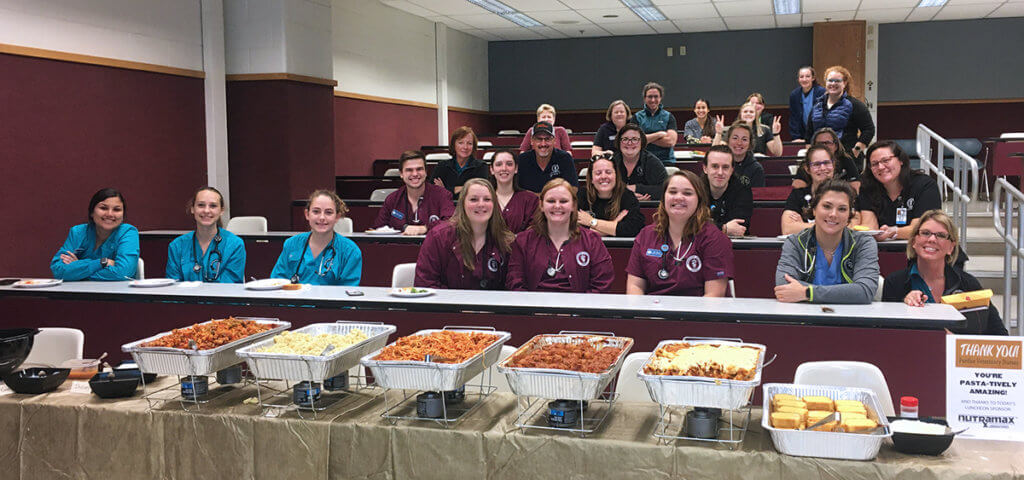 Purdue Veterinary Medicine's veterinary nurses take a group photo before a feast of pasta