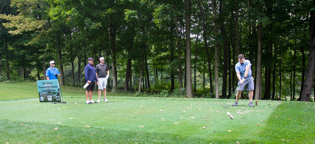 A golfer takes a swing as his teammates watch from the sidelines