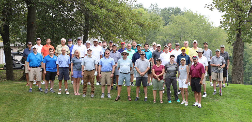 golfers join for a group photo along the golf course at Coyote Crossing
