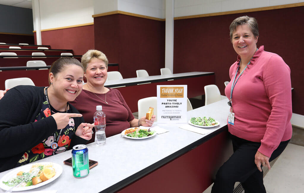 Jennifer points to a sign that reads You're Pasta-tively Amazing joined by Paige and Pam sitting down to eat lunch