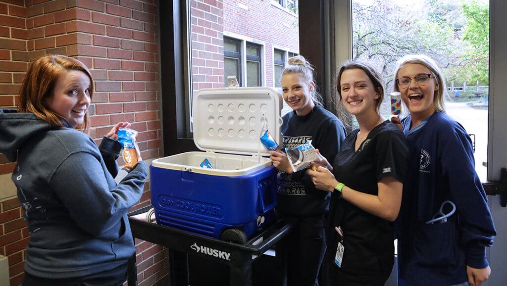 A group of veterinary nurses smile holding ice cream treats