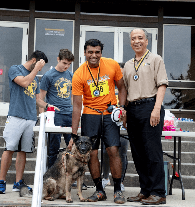 """Dean Willie Reed presented Nithin Raghunathan and his dog with the prize for """"Fastest Human-Canine Pair""""."""