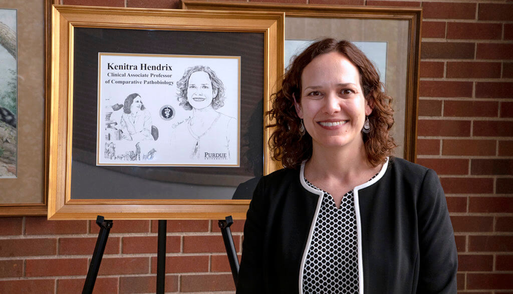 Dr. Hendrix stands beside a framed illustration of her in the Continuum Cafe