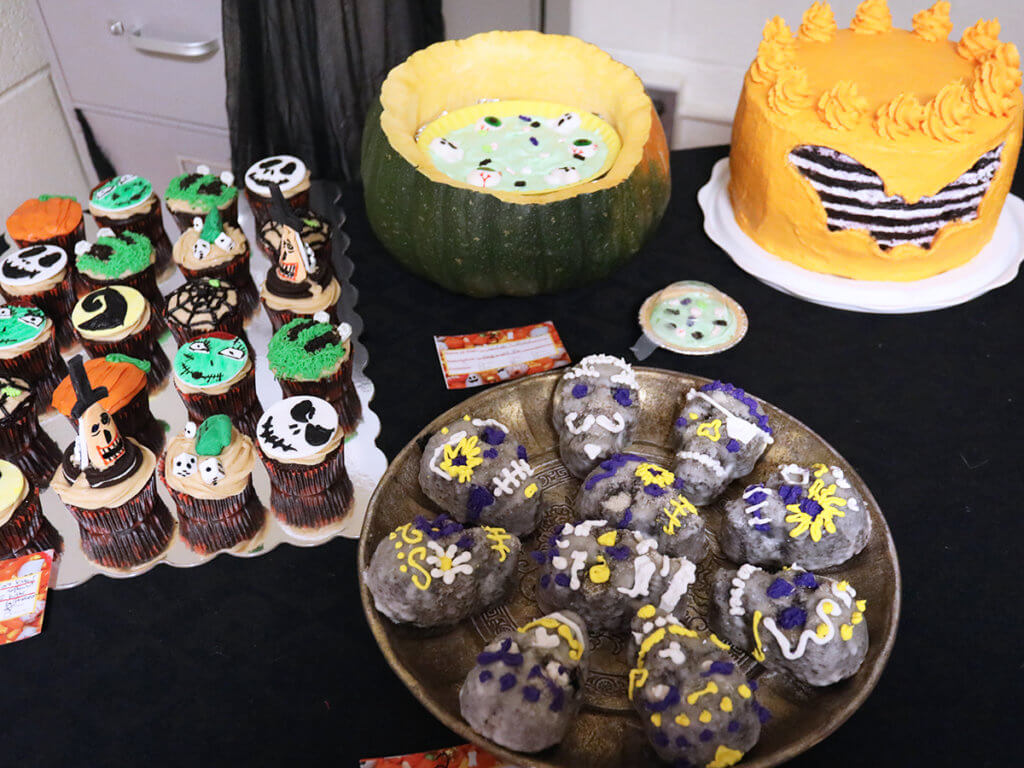Spooky cupcakes, sugar skull cupcakes, keylime pie with fake eyeballs and a bat decorated cake are festively displayed on a table