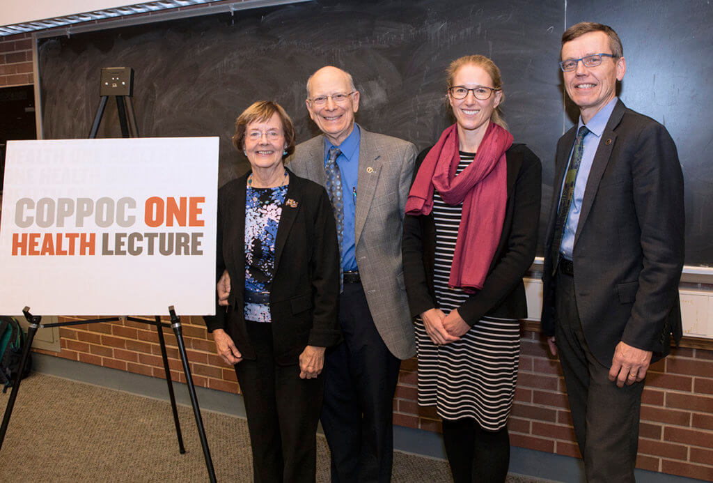 Dr. Coppoc and Harriet stand beside Dr. Plowright and Dr. HogenEsch alongside a sign that reads Coppoc One Health Lecture