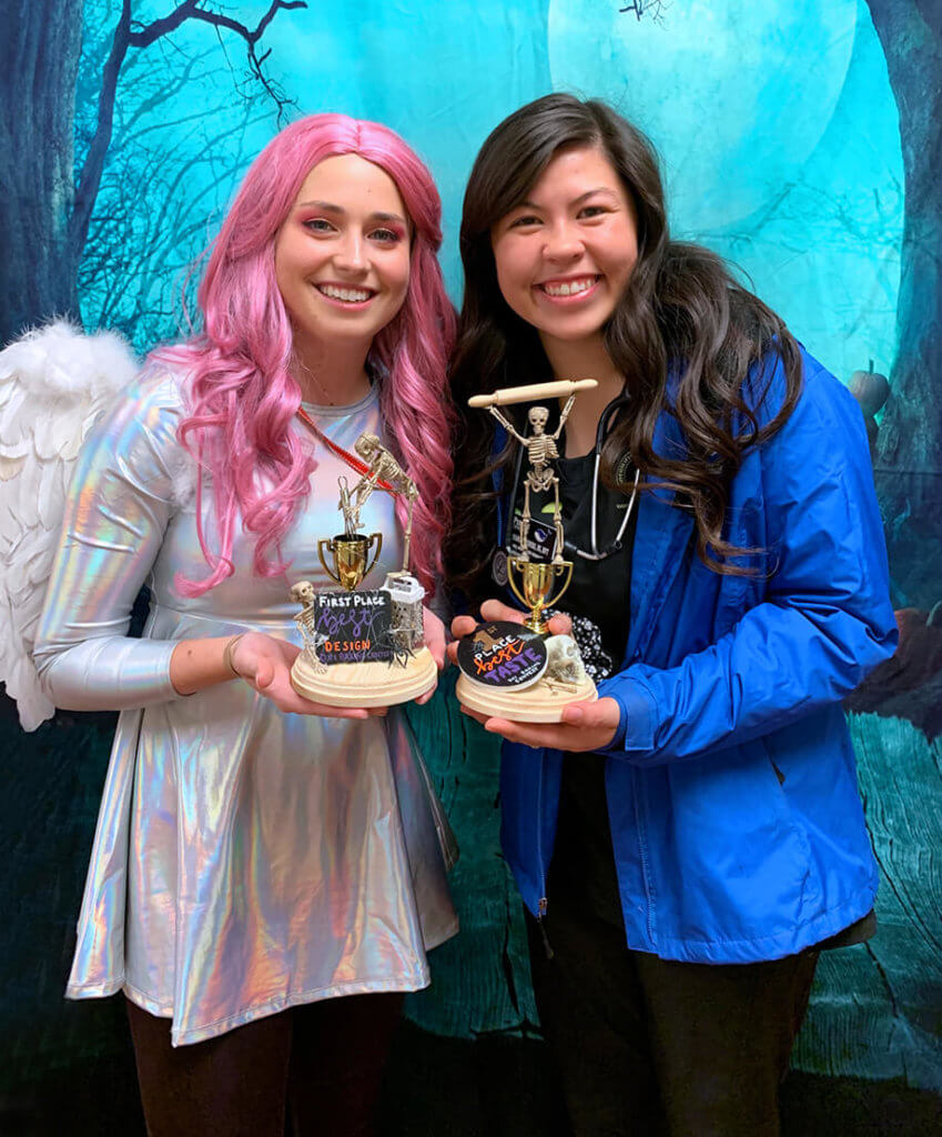 Brittany Rhodes dressed up as an angel and Bri Seiders hold their winning trophies against a spooky Halloween photo backdrop