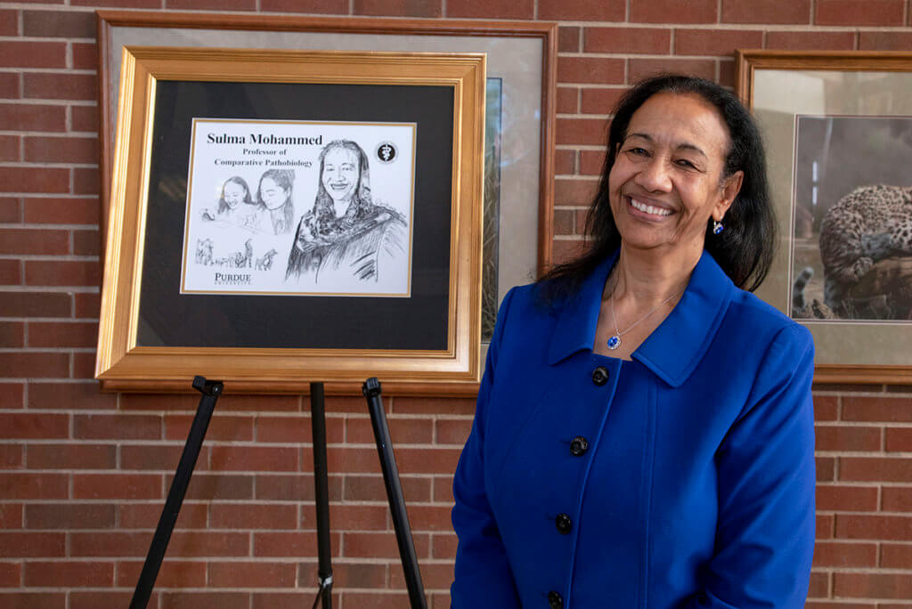 Dr. Mohammed stands next to a framed illustration of herself against a brickwall in the Lynn Hall Continuum Cafe