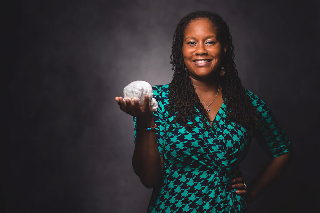 Dr. Lyle pictured against a photo backdrop holding a model of a brain