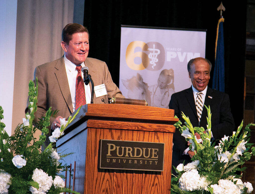 Dr. Adams speaks from behind a podium on stage at the Awards Celebration dinner