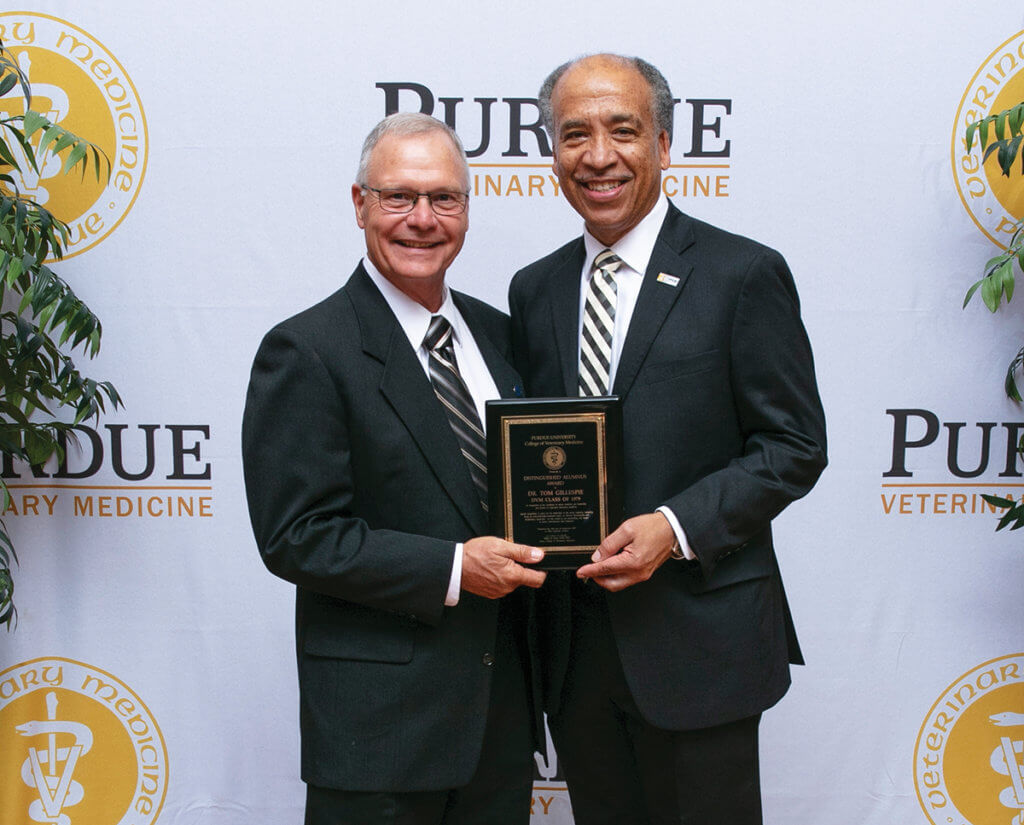 Dr. Gillespie stands beside Dean Reed holding his award plaque