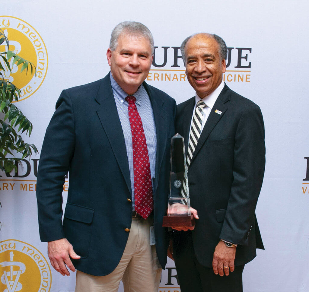 Dr. Christian stands beside Dean Reed holding his award