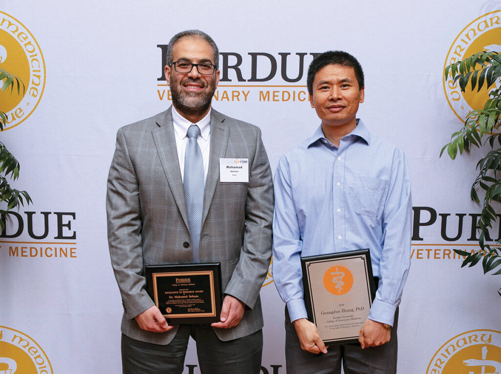 Dr. Seleem stands beside Dr. Zhang holding their respective award plaques