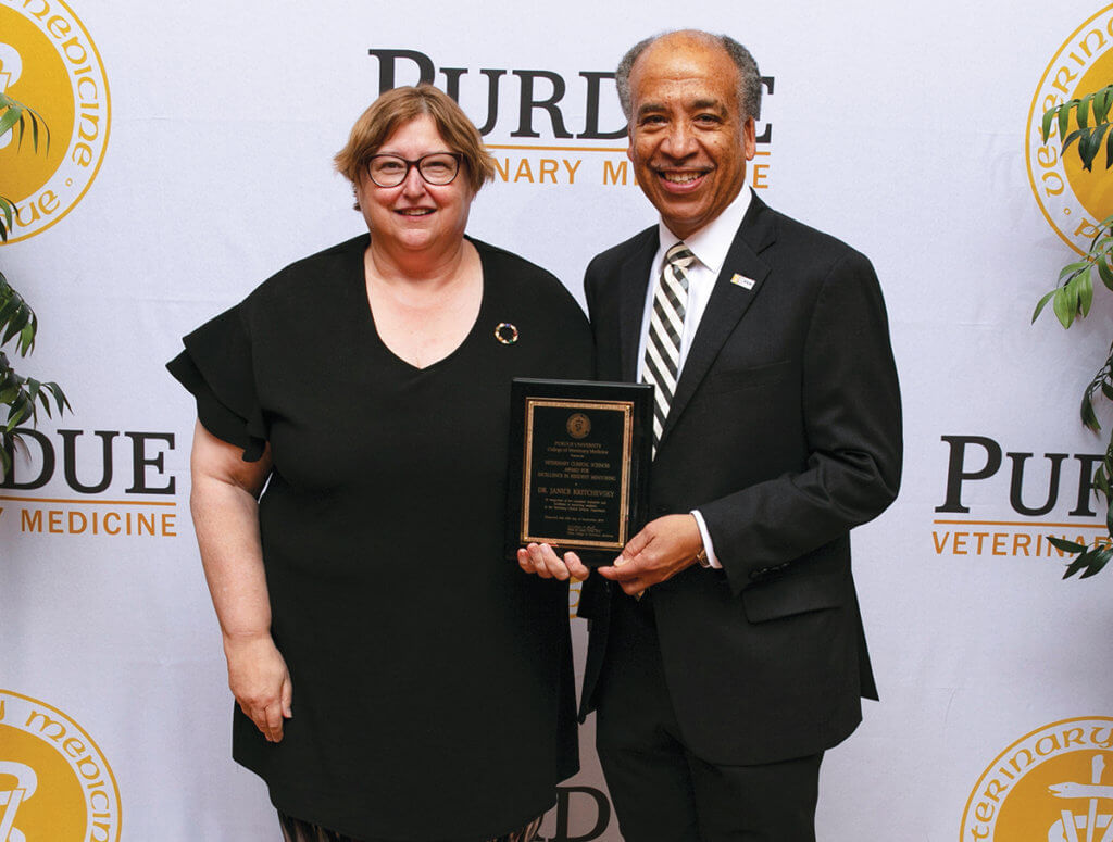 Dr. Kritchevsky stands beside Dean Reed holding her award plaque