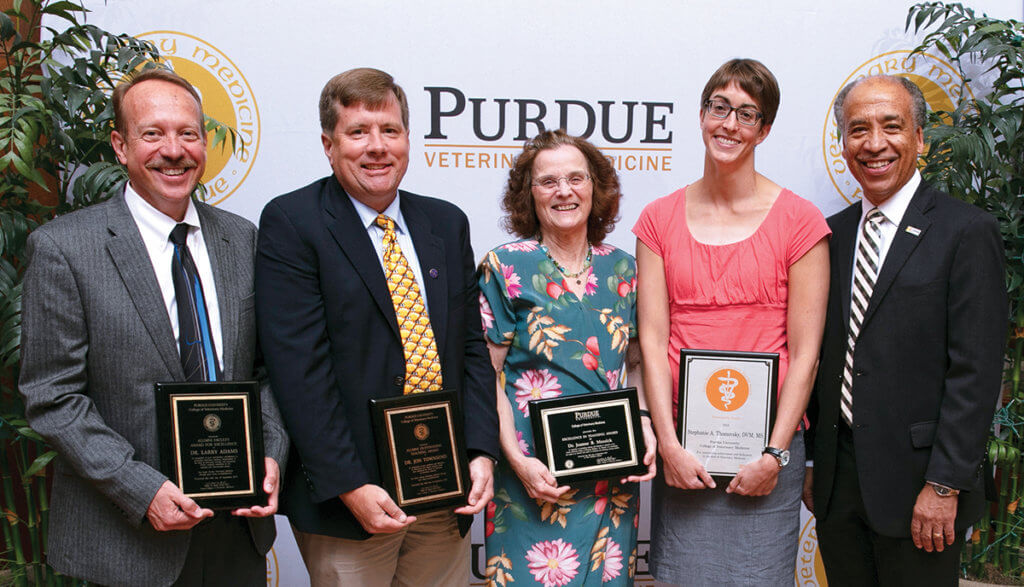The faculty award winners stand together with Dean Reed holding their award plaques