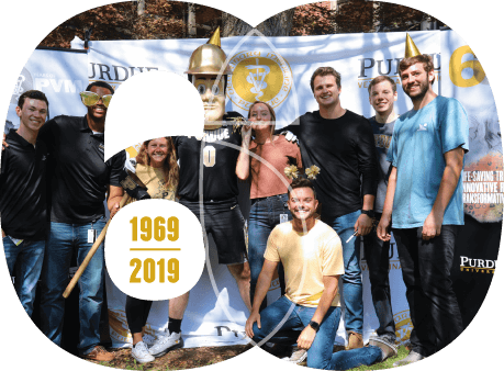 Purdue Pete joins a group of students donning photo props in front of a photo backdrop in the Lynn Hall Courtyard