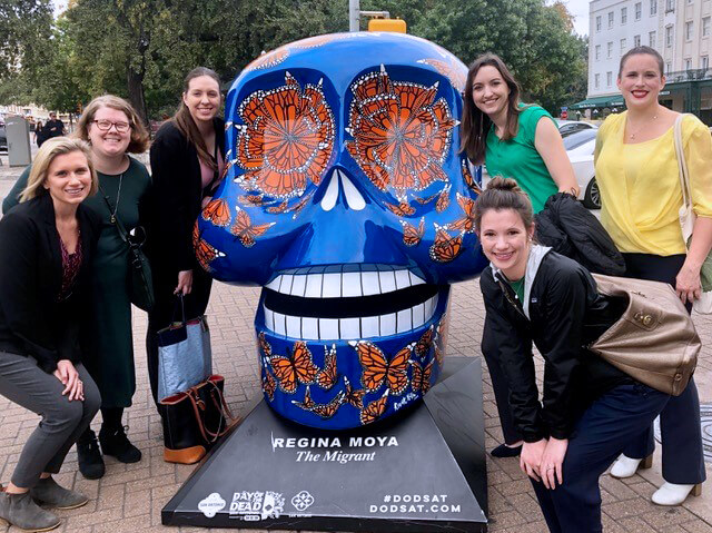 The team of five women group together around a vibrant blue and red skull sculpture in an outdoor plaza