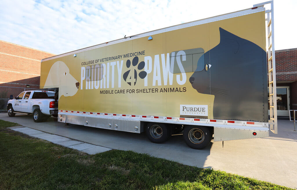 The Priority 4 Paws mobile surgery unit sits parked out the Purdue Veterinary Teaching Hospital against a blue cloud filled sky