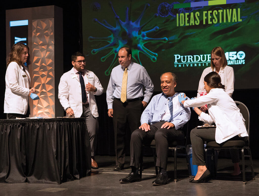 Dean Reed sits on stage as a he receives a flu shot from a Purdue Pharmacy student seated beside him and others look on