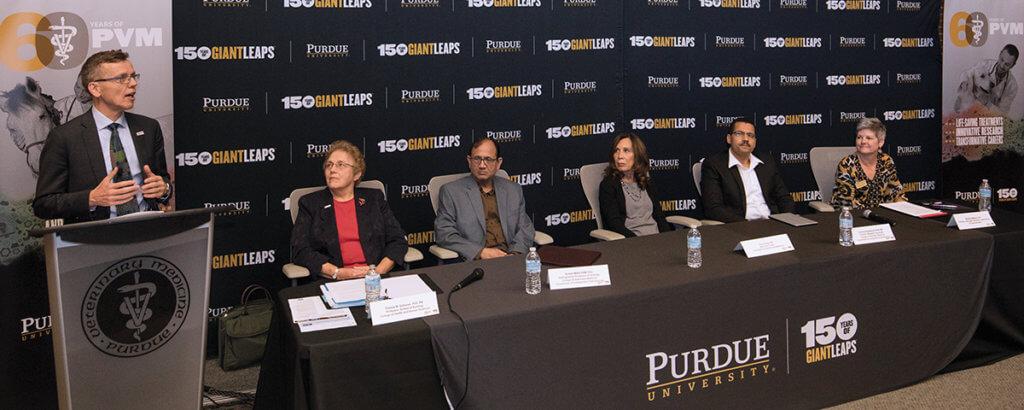 Dr. HogenEsch speaks as the panelists seated beside him listen