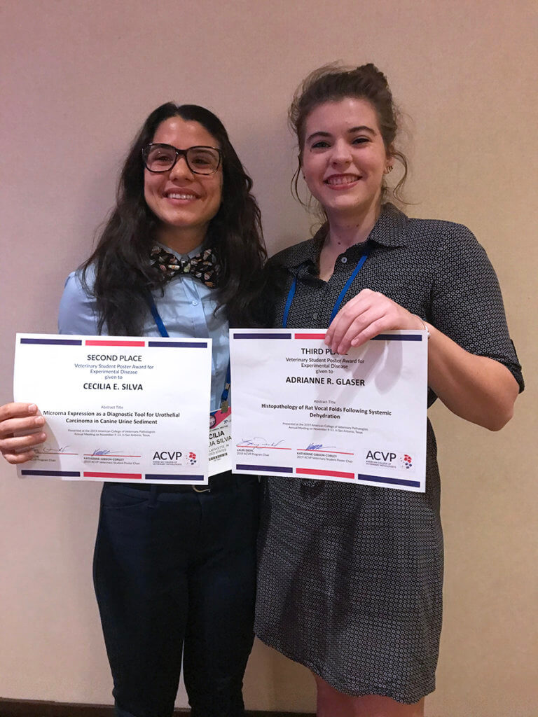 Cecilia and Adrianne stand together holding their award certificates
