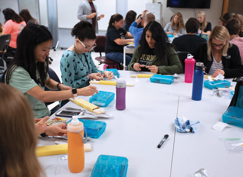 Students sit in table groups practicing suturing