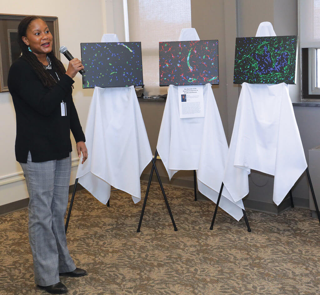 Dr. Lyle speaks into a microphone next to the three canvas prints