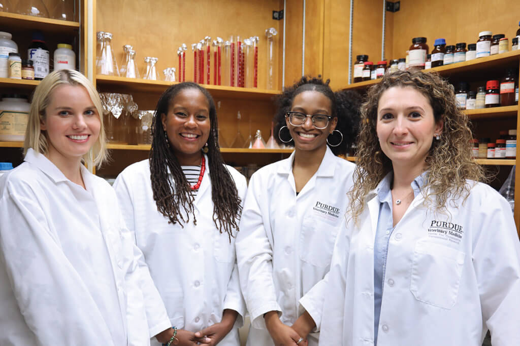 The lab team members stand together wearing white coats with laboratory equipment in the background