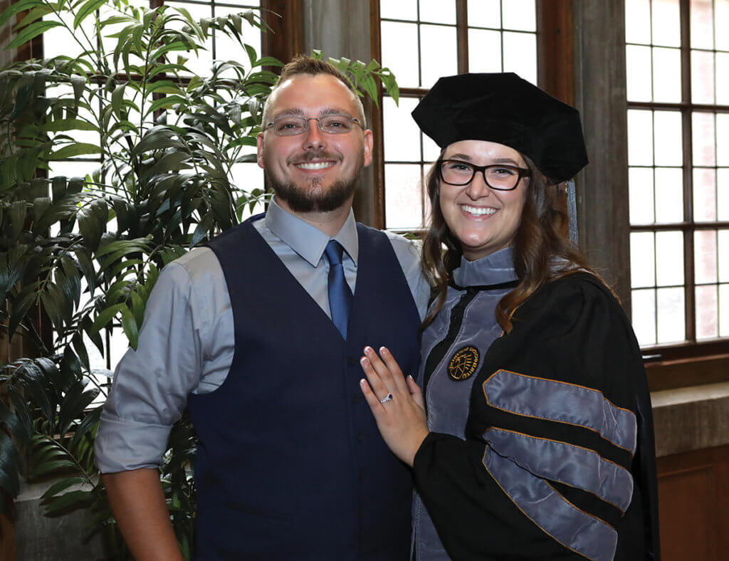 Dr. Taylor is dressed in her cap and gown standing next to her husband against a wall of windows in the Purdue Memorial Union