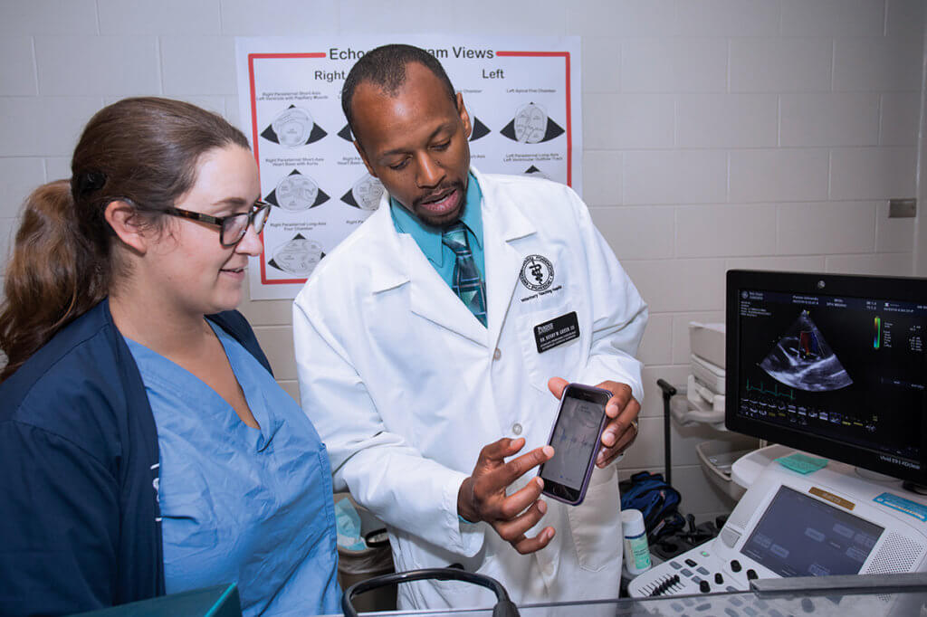 Dr. Green holds a cell phone showing the screen to Taylor