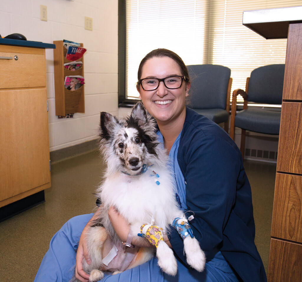 Taylor sits on the floor in a hospital exam room holding a black and white dog in her lap