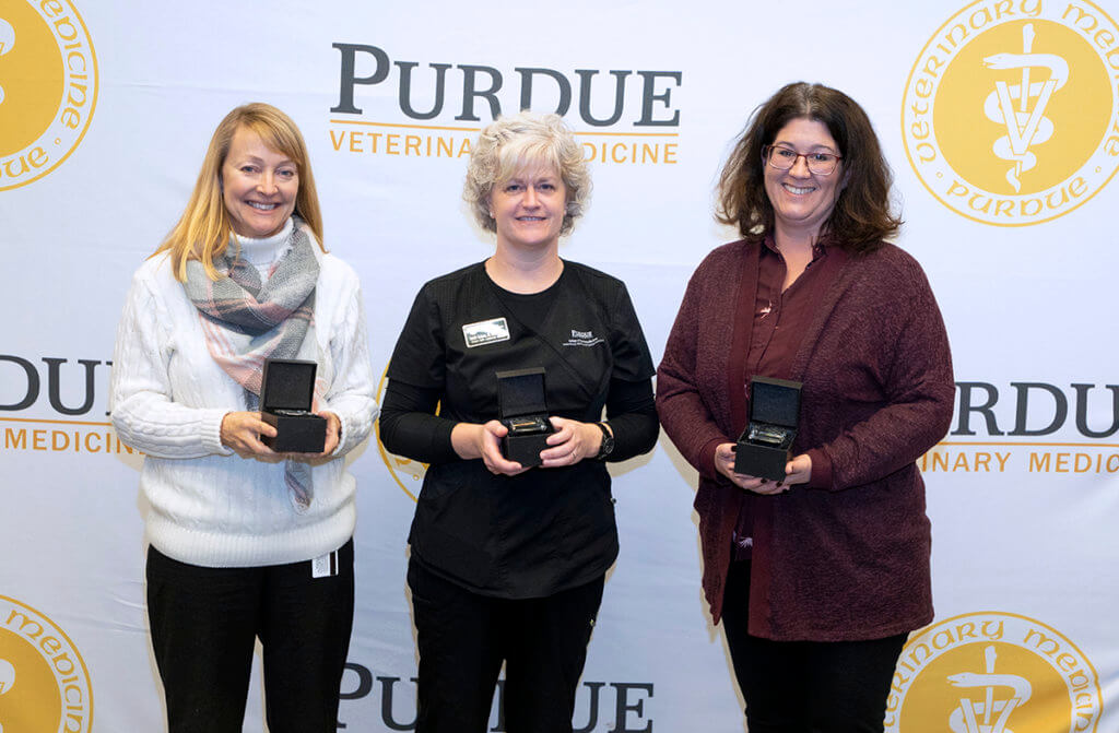 Staff members hold a commemorative gift for 15 years of service to the university
