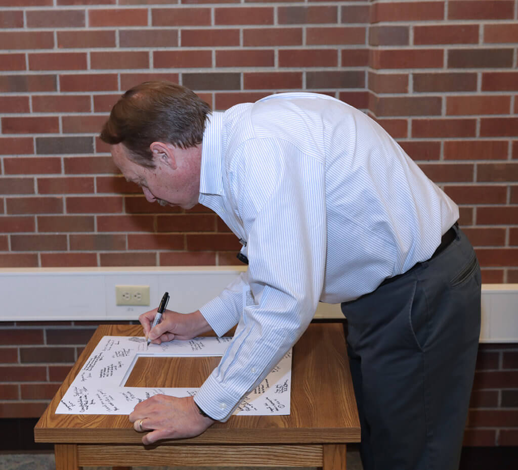 Dr. Larrry Adams signs the photo mat at a small table