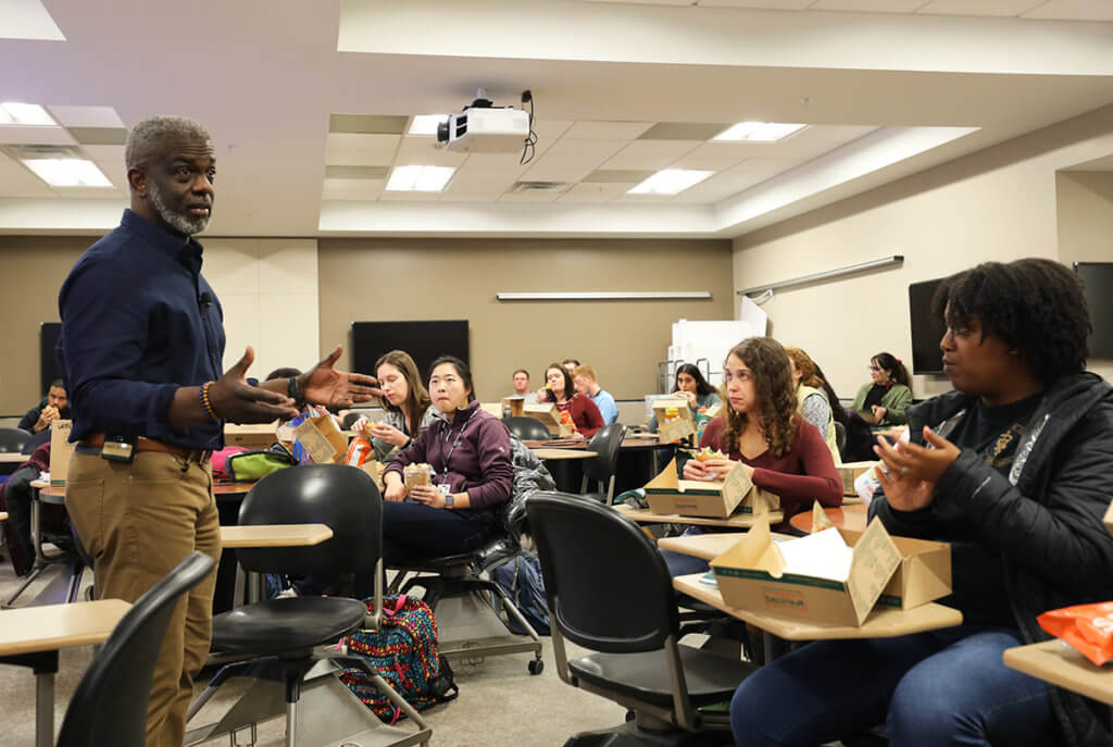 Ralph speaks to students as they eat lunch in a classroom