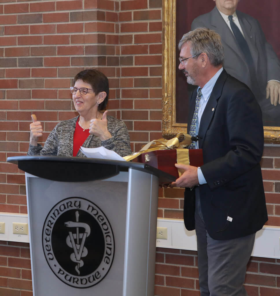 Kris gives two thumbs up to the crowd as Dr. Breur presents her with a gift