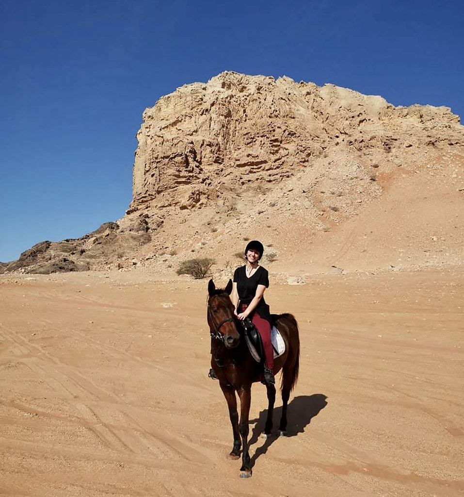 Caitlin sits atop a horse with the desert scape in the background and a clear blue sky