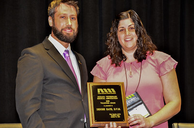 Matt and Denise stand together holding her award plaque