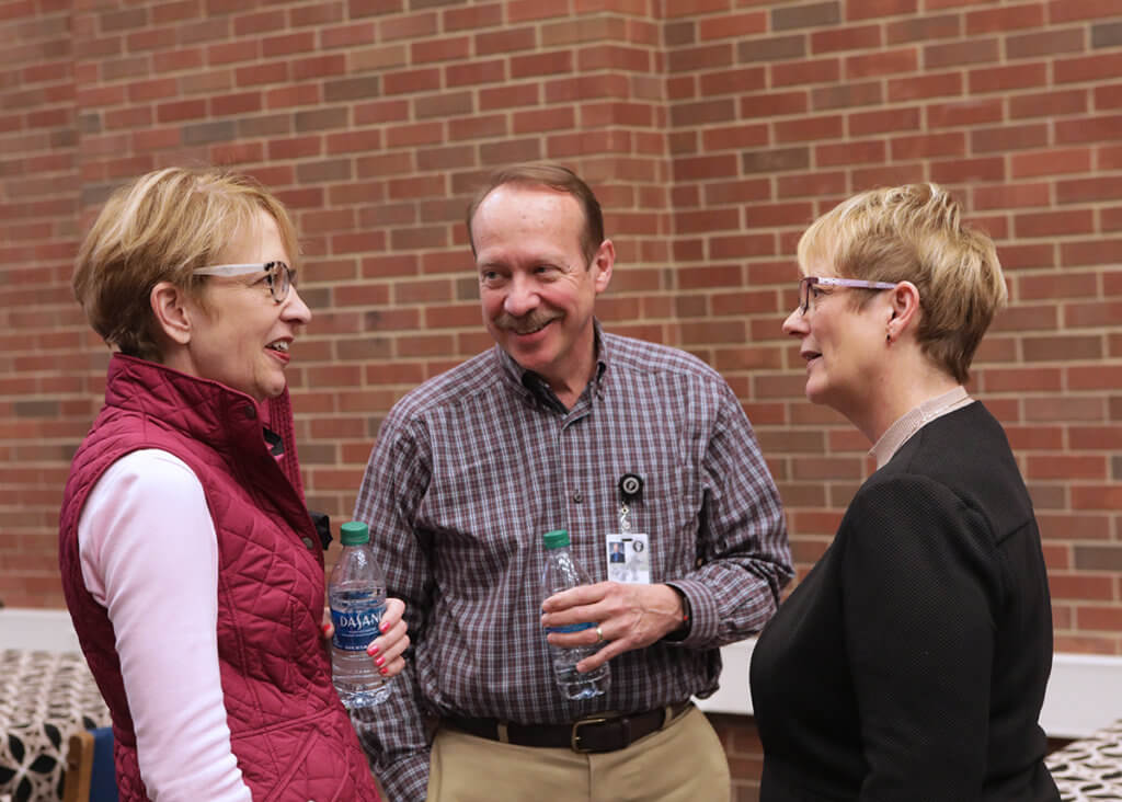 Dr. Lowery speaks with Dr. Laurie Adams and Dr. Larry Adams in the library