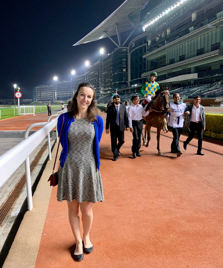 Caitlin stands along the track as a horse and its jockey ride alongside their team in the background