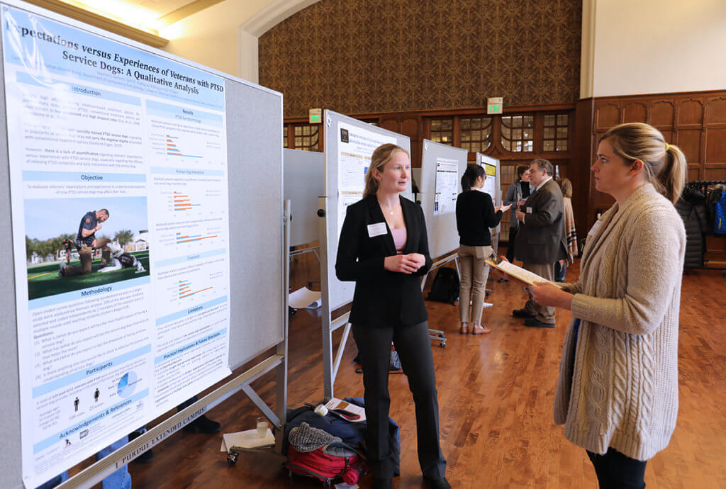 A competition judge looks over the research poster as Leanne stands beside it with other poster judging underway in the background