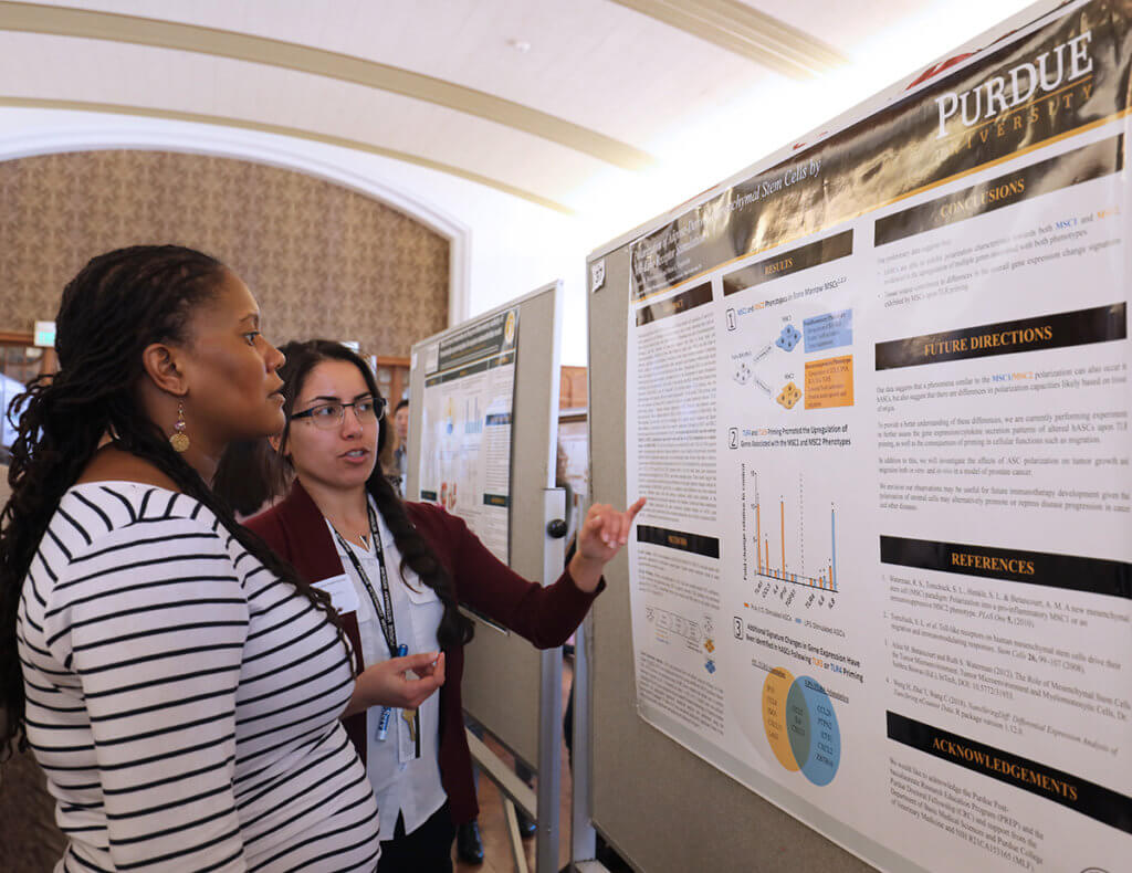 Cosette points to her research poster as speaks to Dr. Lyle