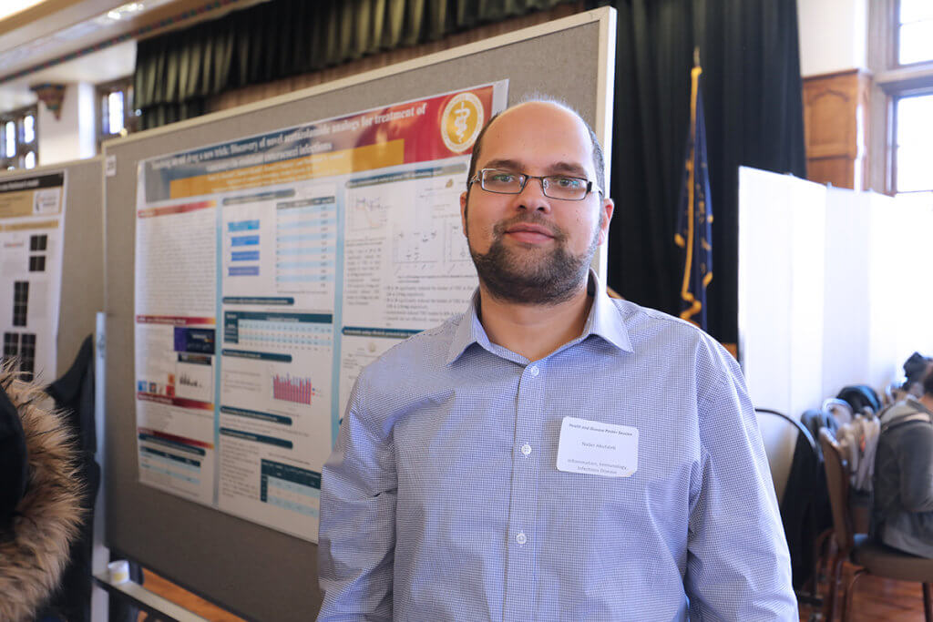 Nader stands in front of his research poster displayed in the Purdue Memorial Union ballroom